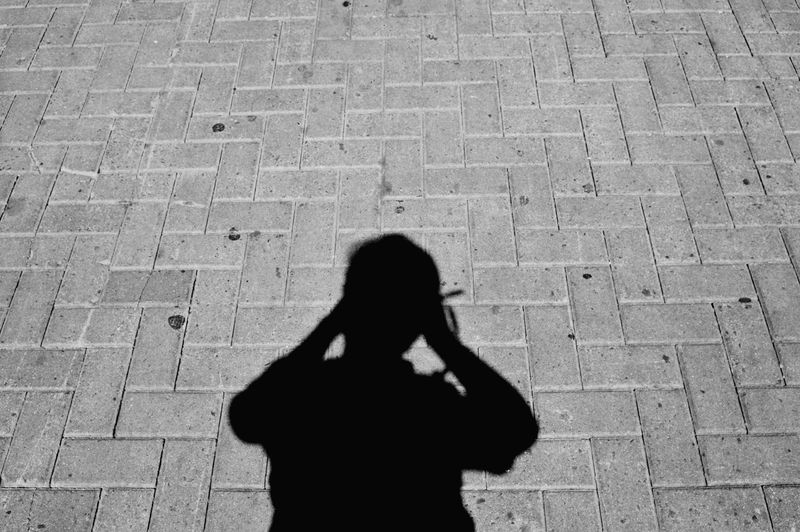 High angle view of silhouette woman standing on cobblestone street