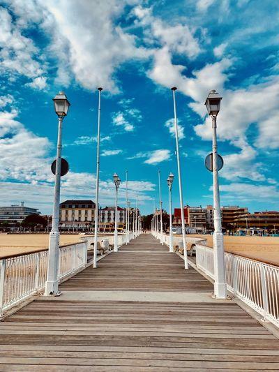 View of boardwalk on bridge against blue sky