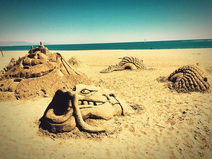 Heart shape on sand at beach against sky