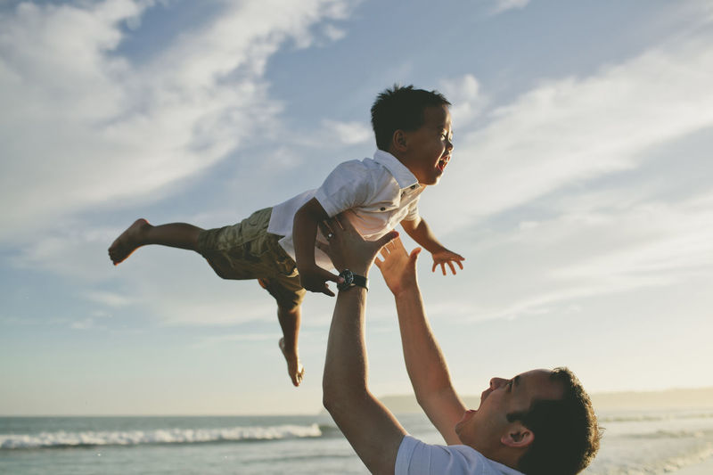 Low angle view of playful father throwing son in air at beach