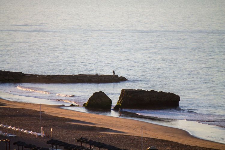 Distant view of man fishing in sea