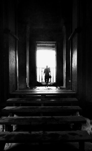Rear view of silhouette woman standing at staircase in building