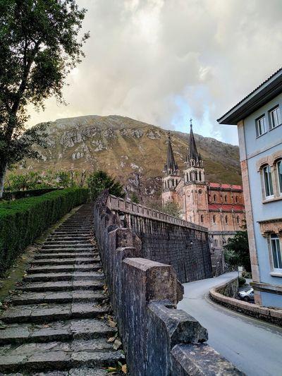 Footpath amidst buildings against sky