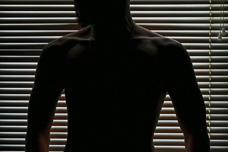 Shirtless Silhouette Man Standing Against Window Blinds