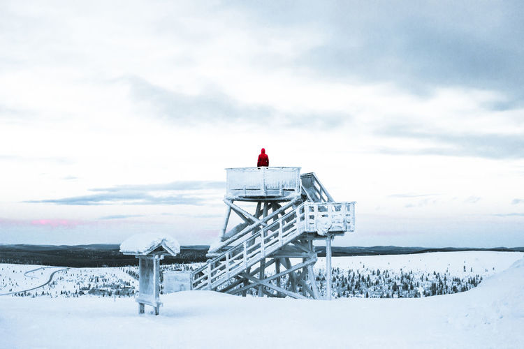 Built structure on snow covered field against sky