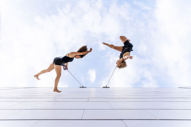 Low angle view of people jumping against sky