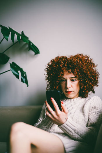 Young woman with curly red hair, looks at smartphone screen, sitting on sofa Hairstyle Using Phone Real People Curly Hair Technology Communication Young Women Portable Information Device Leisure Activity Wireless Technology Mobile Phone One Person Young Adult Lifestyles Indoors  Smart Phone Sitting Vertical Plant Monstera Deliciosa Copy Space