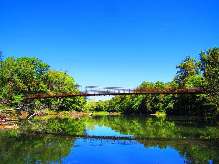 Bridge over lake against blue sky