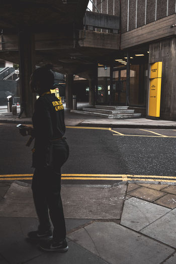 Rear view of man standing on sidewalk