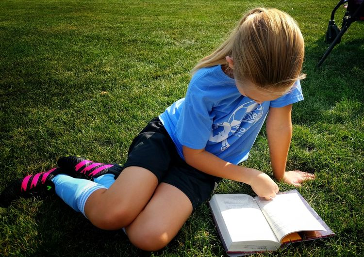 Grass Child Childhood High Angle View One Person Outdoors Reading A Book Soccer Lying Down waiting foenher soccer game, my daughter would rather read thsn anything else