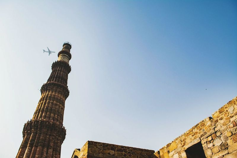 Low angle view of qutb minar against airplane flying in clear sky