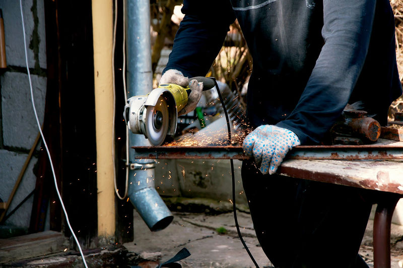 Low section of man working on metal