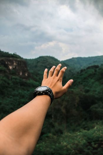 Cropped hand of person against mountain and sky