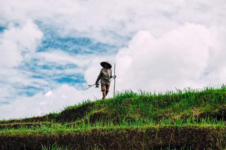 Woman standing and working on rice field against sky