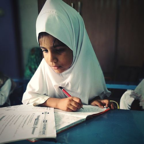 Close-up of girl wearing hijab while studying