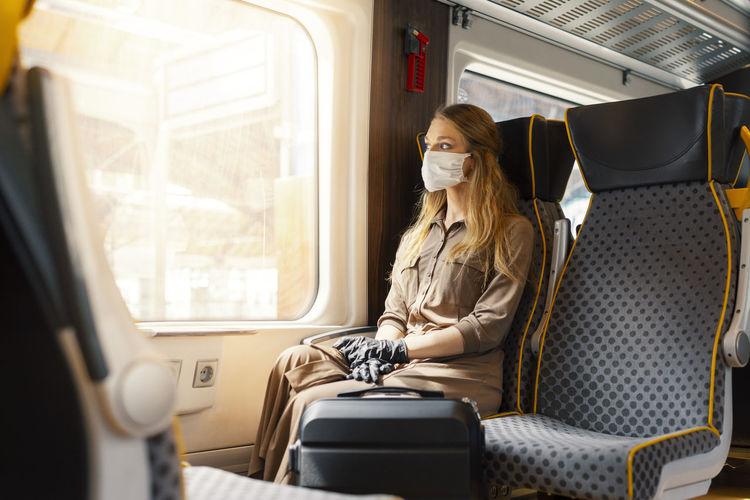 Woman wearing mask sitting on seat in train