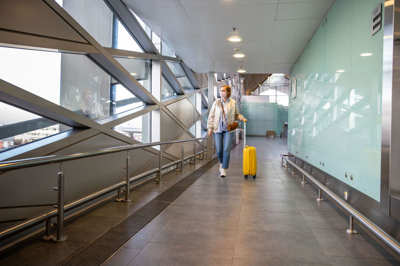 Full length of woman wearing mask carrying luggage at corridor of building