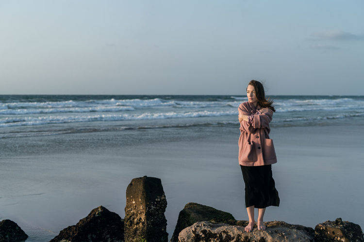 Full length of woman standing on rock at beach against sky