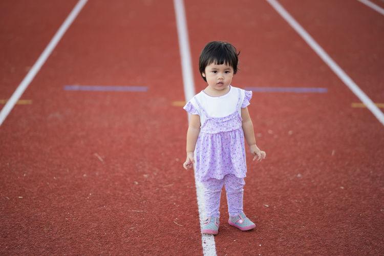 Full length portrait of cute girl standing on running track