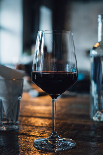 Glass of red wine in restaurant Alcohol Close-up Drink Drinking Glass Focus On Foreground Food And Drink Freshness Glass Glass - Material Household Equipment Indoors  No People Red Wine Refreshment Still Life Table Transparent Wine Wineglass Wood - Material