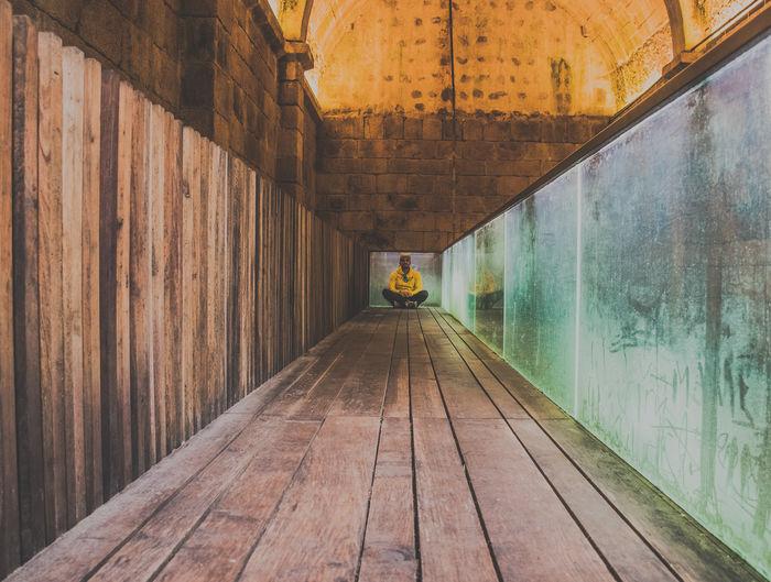Man Sitting In Wooden Corridor