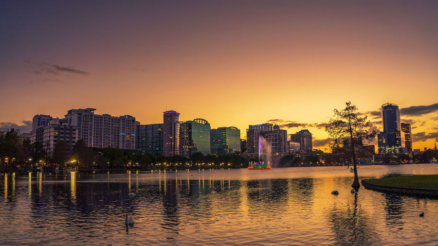 River by illuminated buildings against sky during sunset