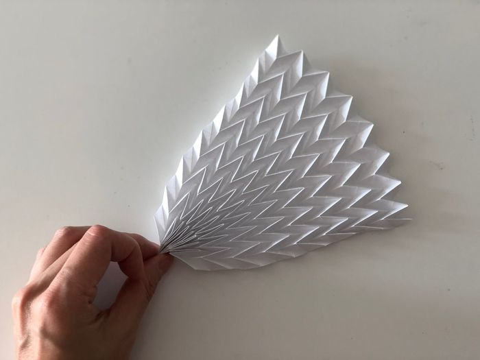 Cropped image of hand holding origami art work on wall