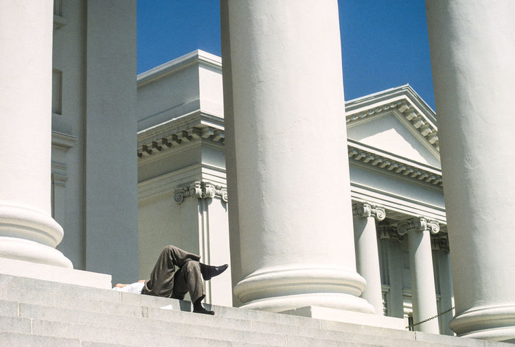 Low Section Of Man Relaxing On Steps At Historic Building