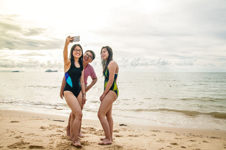 Happy teenagers taking selfie on the beach Asian  Fun Happy Taking Photo Teenagers  Beach Day Friendship Full Length Happiness Leisure Activity Lifestyles Outdoors Sand Sea Smiling Standing Taking Selfie Teen Teenage Boy Three People Togetherness Vacations Young Adult Young Women Step It Up Summer Exploratorium