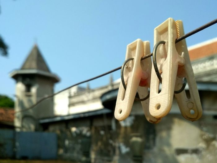 Low angle view of clothespins hanging on rope against buildings and sky