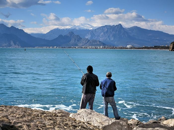 Men Fishing While Standing On Rocky Shore Against Mountains