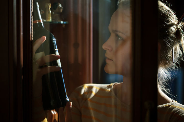 Young woman looking at wine bottle seen through glass
