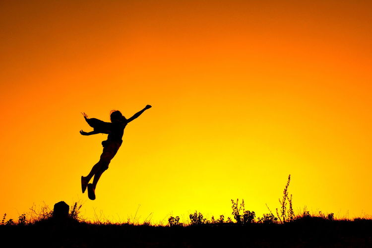 Silhouette Person Jumping In Mid-Air Against Orange Sky