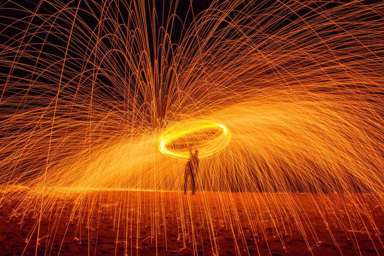 Light painting on illuminated fire at night