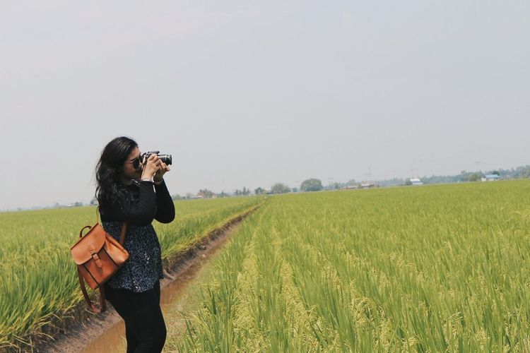 Full length of woman photographing in field against clear sky