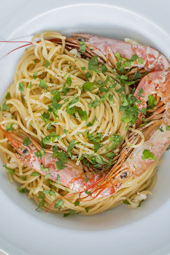 A white plate with spaghetti with king prawn.