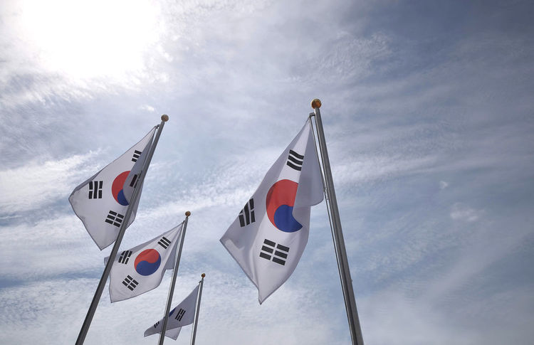 South Korea / Flags No People Flag White Color Text Communication Outdoors Sign Number Pole Patriotism Guidance Western Script Sky Cloud - Sky Low Angle View Nature Day Transportation Shape Independence Hall Independent  Korean Victory Country