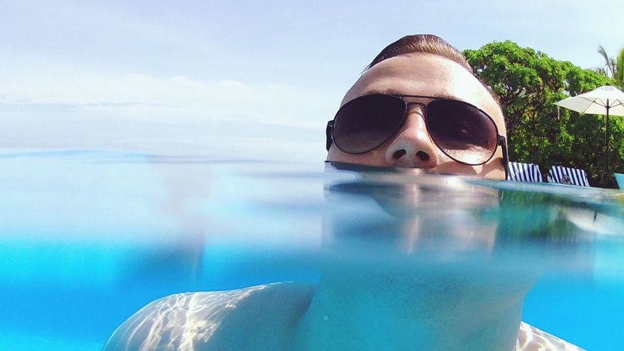 Portrait of man wearing sunglasses while swimming in infinity pool