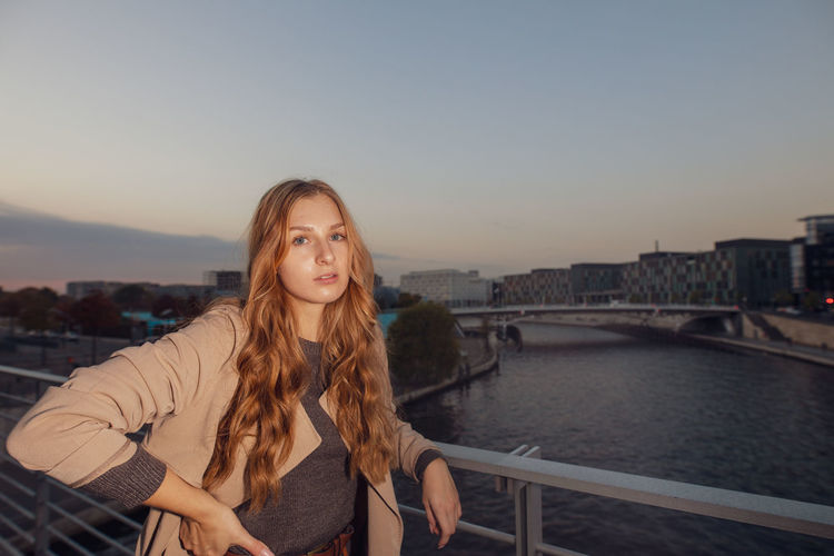 Portrait Of Beautiful Woman Standing By Railing Against Sky During Sunset