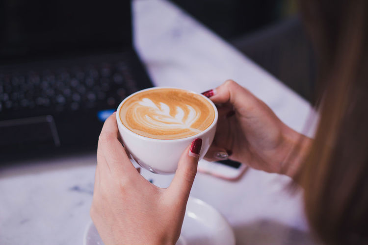 Cropped image of woman holding coffee cup