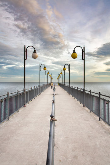 Street light on pier against sky