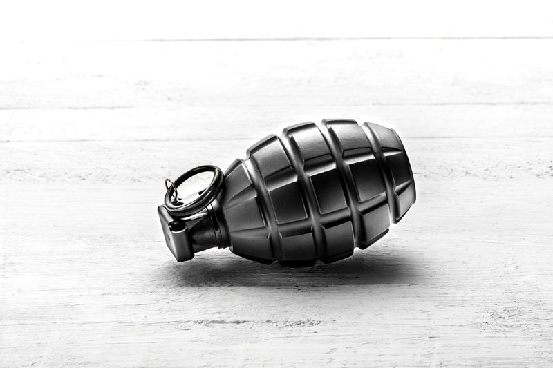 Hand grenade with the pin in lying on its side on a white wooden board centered with copy space Grenade Army Canister Combat Hand Grenade Lethal Lying Down Military Pink Color Safety Terrorism War Weapon