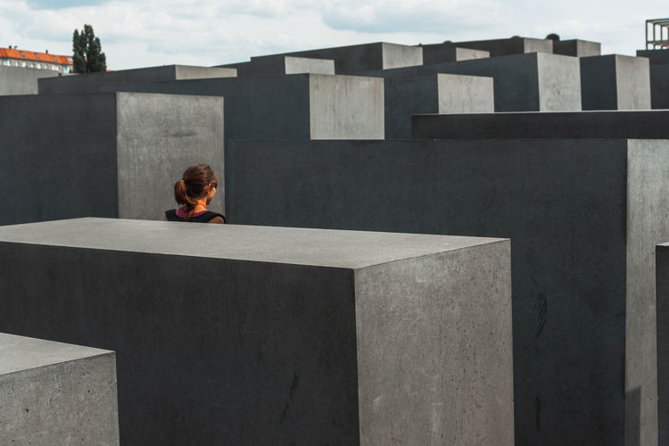 Woman sitting on retaining wall