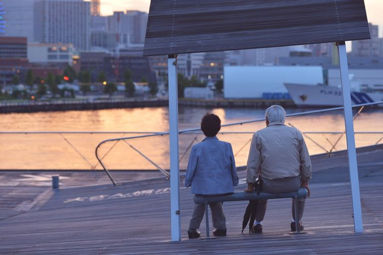 Rear view of two people sitting on bench