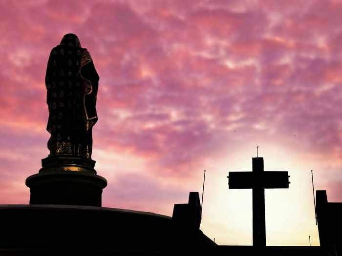 Silhouette of the large Saint Ann statue and cross on church with blurred sunrise sky background on architecture design and art of religion concept Saint Ann Cross Top Of Blur Background Sunrise Cloud - Sky Colorful Shadow Silhouette Outdoor Low Angle View Religion Faitp EyeEm Selects City Sunset Statue Sculpture Silhouette History Sky Architecture Building Exterior Built Structure Romantic Sky Dramatic Sky Ancient Civilization Place Of Worship Catholicism Church
