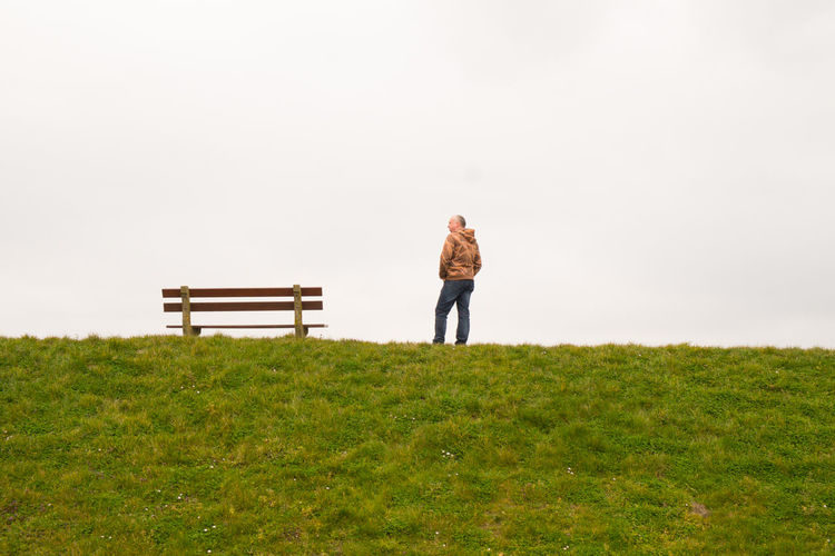 A single person standing next to a single empty wooden bench on the horizon above a grass field against a large grey clouded sky depicting loneliness, thinking, pondering, grieve, being alone, sadness Full Length Adult One Person Rear View Plant Nature Standing Grass Casual Clothing Land Men Emotion Day Field Copy Space Environment Contemplation Landscape Solitude Outdoors Looking At View