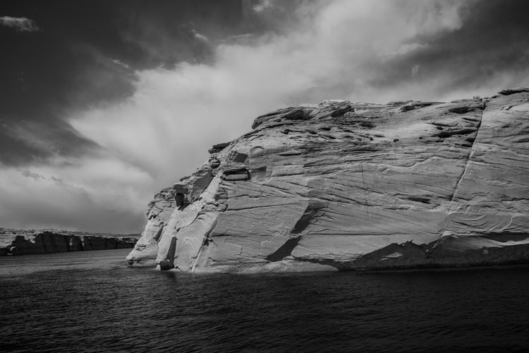Rock formations by lake powell against sky