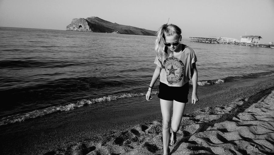 Monochrome Photography Standing Beach Sea Beach Water Shore Person Standing Leisure Activity Casual Clothing Lifestyles Vacations Full Length Horizon Over Water Sand Scenics Tranquil Scene Summer Beauty In Nature Sunglasses Tranquility Non-urban Scene