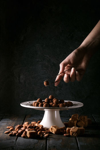 Cropped hand with sweet food at table against wall