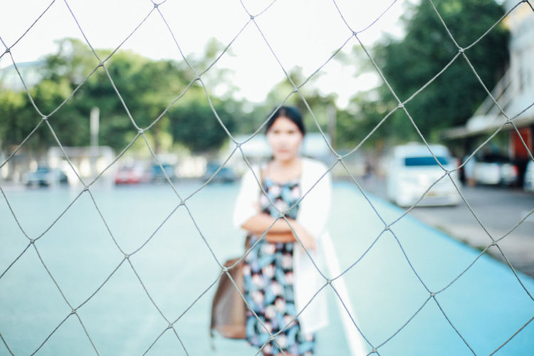 Portrait of young woman standing on court seen through net